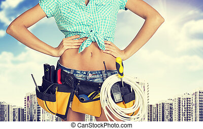 Woman in tool belt standing akimbo. Cropped image. High-rise...
