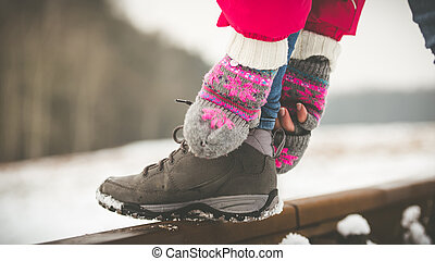 Girl tying shoe laces on the rails in winter