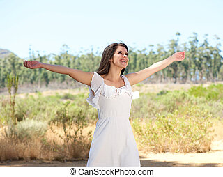 Happy young woman smiling with arms spread open - Portrait...
