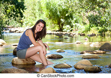 Happy young woman sitting by stream with feet in water -...