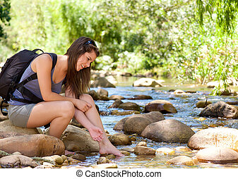 Young woman sitting by stream with backpack - Happy young...