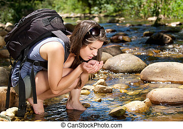 Woman hiker with bag drinking water from stream in nature -...