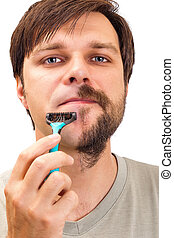 Closeup portrait of a young man shaving his beard isolated...