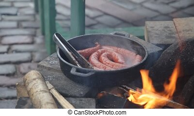 Appetizing sausages are fried on a big frying pan on the...