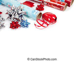 Assorted Christmas wrapping paper and ribbons on a white...