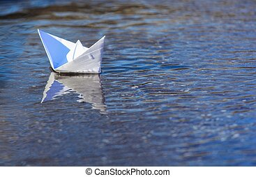 White Paper Boat Sailing on Blue Flowing Water