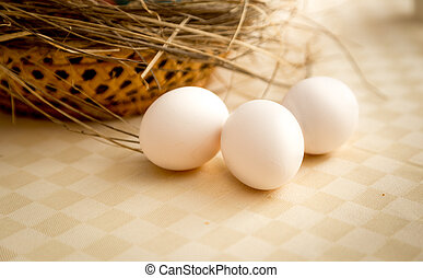 Closeup shot of three white eggs lying on table next to...