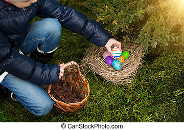 Closeup shot of little girl putting painted egg in basket -...