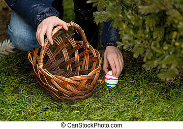 Closeup shot of girl putting colorful Easter egg in the...