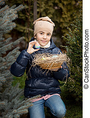 happy girl showing Easter egg she found on backyard -...