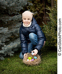 smiling girl collecting Easter eggs at backyard - Cute...