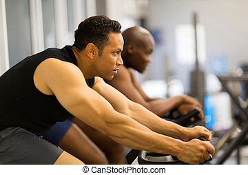 men working out with stationary bike - fitness men working...