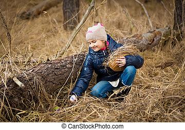 girl reaching for Easter egg under log in forest - Little...