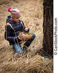 girl having Easter egg hunt at forest - Little girl having...