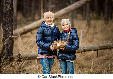 happy sister posing with Easter basket with eggs - Portrait...
