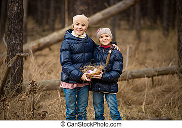 two happy girls holding basket full of Easter eggs - Closeup...