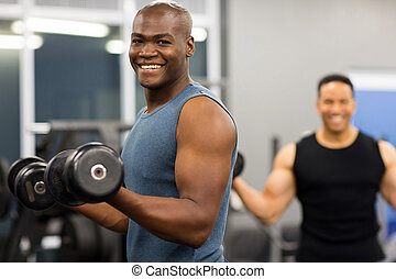 african man working out with dumbbells - healthy african man...