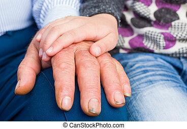 Reassuring hand - Photo of a child hand on elderly man hand