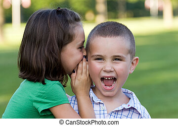 Kids Telling Secrets - A young girl telling her brother a...