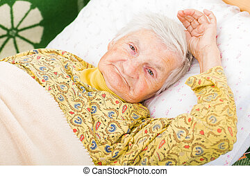Elderly woman - Sweet smiling elderly woman resting in bed