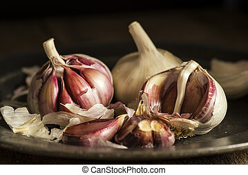 Fresh garlic cloves in moody natural lighting set up with...