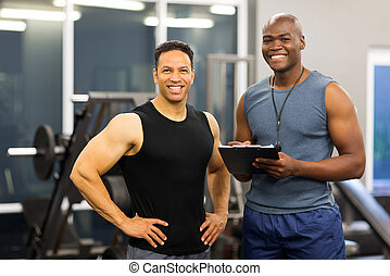 african american fitness instructor with client - portrait...