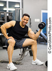 man lifting weights  - cheerful man lifting weights at gym