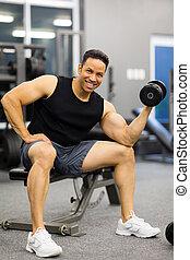 man lifting weights  - cheerful man lifting weights at gym
