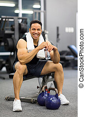 mid age man sitting on bench after exercise