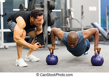 personal trainer motivates client doing push-ups