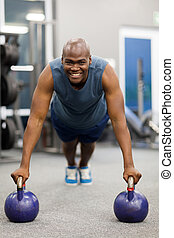 african american man in plank position with kettle bells