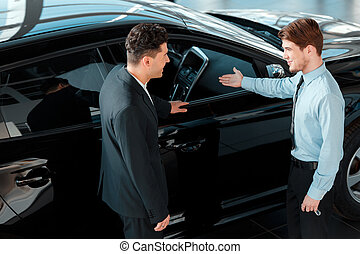 Handsome young man in dealership - Salesman and customer....