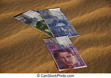 Swiss currency bank notes laying on sand