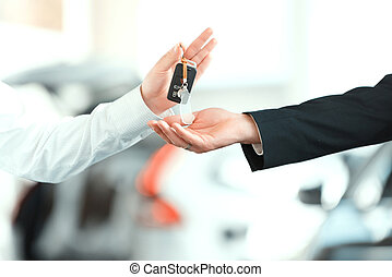 Handsome young man in dealership - Here is your key. Closeup...