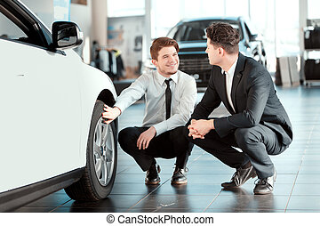 Handsome young man in dealership - Go for a drive. Young...