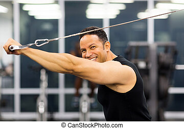 mid age man working out with pull-down machine - side view...
