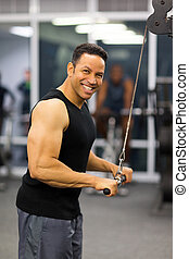 man using triceps pull down - muscular man using triceps...
