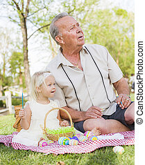 Grandfather and Granddaughter Coloring Easter Eggs on Blanket At