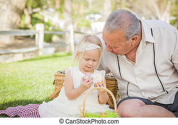 Grandfather and Granddaughter Enjoying Easter Eggs on Blanket At