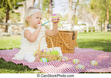 Cute Baby Girl Coloring Easter Eggs on Picnic Blanket - Cute...