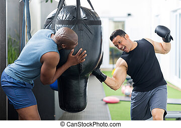 man training with punch bag in gym