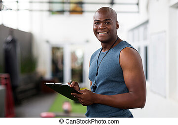 african american male trainer with clipboard - handsome...