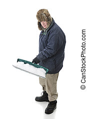 Senior Snow Shoveler - Full length image of a bunded senior...