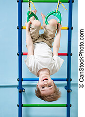 child boy hanging on gymnastic rings at home