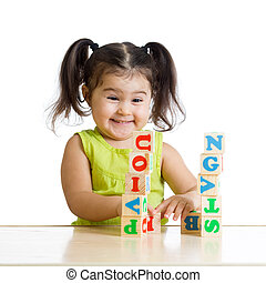 smiling little girl is building a toy block sitting at table