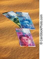 swiss currency bank notes laying on desert sand