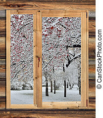 Snowy winter landscape in the frame of a rustic wooden...