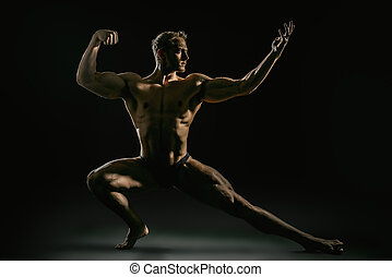 leg dark - Athletic muscular man posing over black...