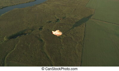 Flying hot air balloon casts shadow on ground - View of...
