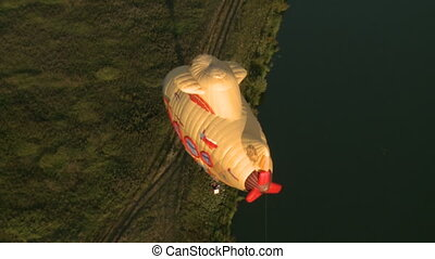 Top view of hot air balloon flying over ground